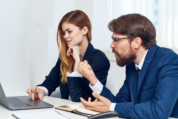 Manager unterhalten sich im büro vor einem laptop beamte