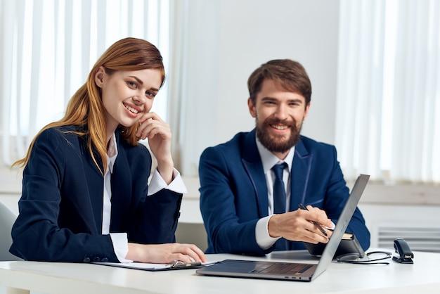 Manager von mann und frau unterhalten sich am tisch vor laptop-team-technologie