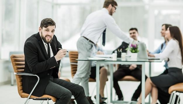 Manager vor dem hintergrund des im büro arbeitenden geschäftsteams