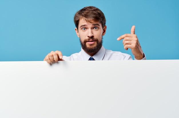 Manager weißes mockup-poster in der hand, das blauen hintergrund annonciert. foto in hoher qualität