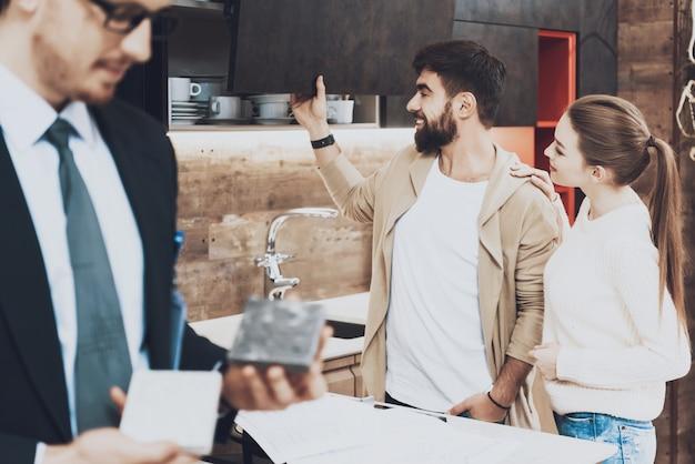 Manager zeigt verschiedene materialien mit paar kunden im hintergrund im küchengeschäft.