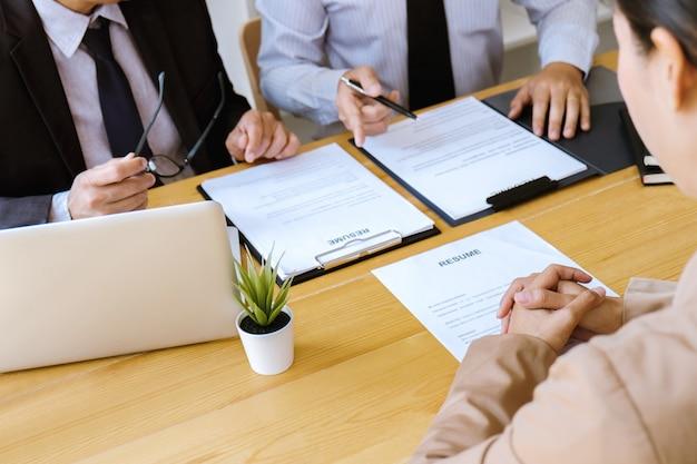 Manager zwei, der einen lebenslauf während eines vorstellungsgesprächs, arbeitgeber interviewt, um weiblichen arbeitssuchenden zu fragen liest