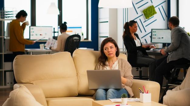 Managerfrau, die auf der couch sitzt und laptop hält und während der virtuellen konferenz im modernen büro des geschäfts über videoanrufe spricht. diverse mitarbeiter, die ein neues finanzprojekt in einem modernen unternehmen planen