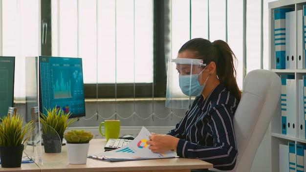 Managerfrau, die einen gesichtsschutz gegen coronavirus-eingabe auf dem computer trägt, der neue statistikdaten analysiert, die in einem neuen normalen finanzbüro arbeiten. freiberufler in einem unternehmen, das soziale distanz respektiert.