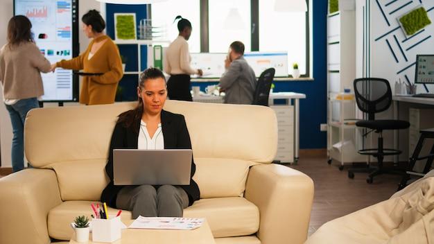 Managerfrau, die laptop hält, im internet schaut, während sie auf der couch sitzt und lächelt wegen guter nachrichten. multiethnische mitarbeiter, die in einem modernen büro über ein startup-finanzunternehmen sprechen.