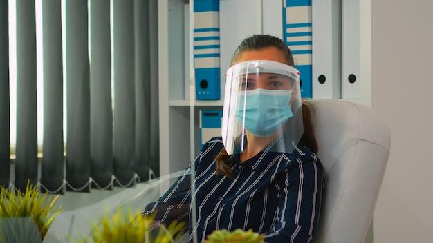 Managerfrau mit visier und schutzmaske, die die kamera im neuen normalen geschäftsbüro lächelt. freiberufler, der in einem finanzunternehmen arbeitet und die soziale distanz während der globalen pandemie respektiert.