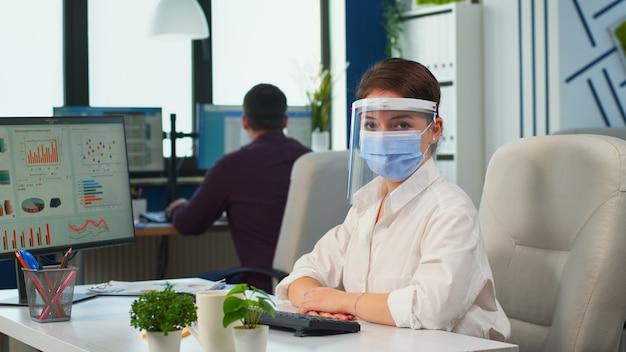 Managerfrau mit visier und schutzmaske, die die kamera im neuen normalen geschäftsbüro lächelt. geschäftsteam, das in einem finanzunternehmen arbeitet und die soziale distanz während der globalen pandemie respektiert.