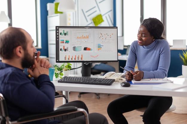 Managerin, die mit finanzdokumenten arbeitet, die diagramme überprüft, die mit gelähmten teamleitern mit behinderungen sprechen, berichte lesen, die im rollstuhl im büro eines start-up-unternehmens sitzen