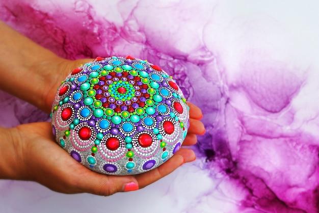 Mandala rock in händen halten