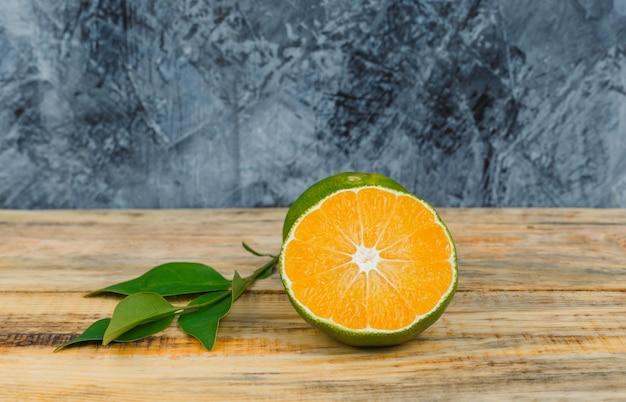 Mandarine mit blättern in einem holzbrett