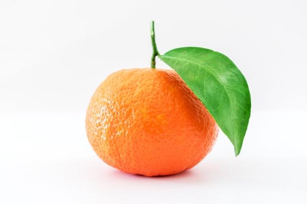 Mandarine oder clementine mit grünem blatt auf weißer oberfläche isoliert