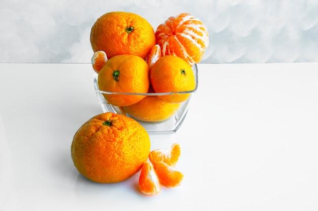 Mandarine oder mandarine auf einem weißen tisch. mandarinen in einer glasschüssel. mandarinenscheiben. zitrusfrüchte