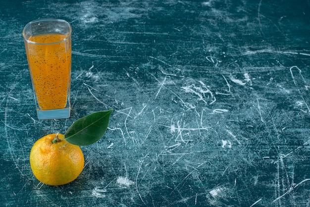 Mandarine und ein glas saft auf dem blauen hintergrund. hochwertiges foto
