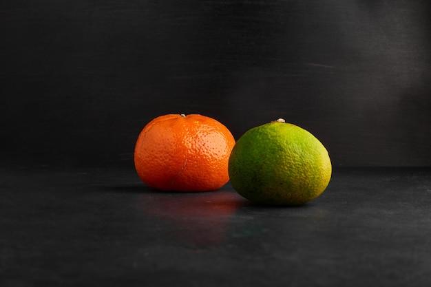 Mandarine und orangen isoliert auf schwarzem hintergrund.