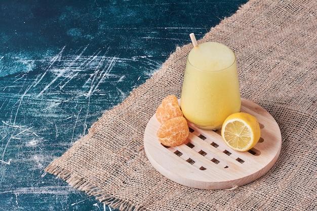 Mandarine und zitrone mit einer tasse getränk auf blau.