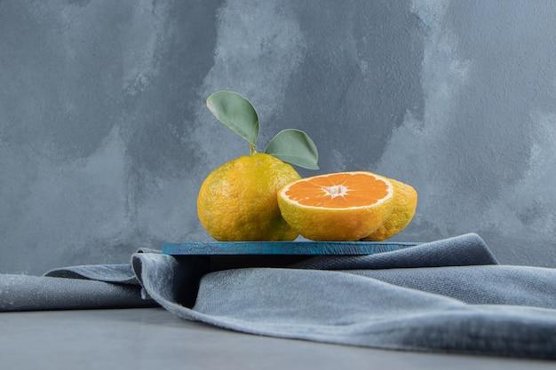 Mandarinen auf einem blauen brett auf einem stück stoff, auf marmor
