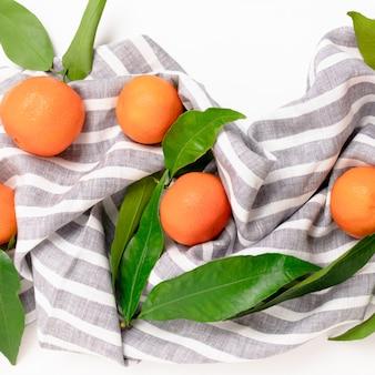 Mandarinen auf einem gestreiften leinentuch auf einem weißen hintergrund