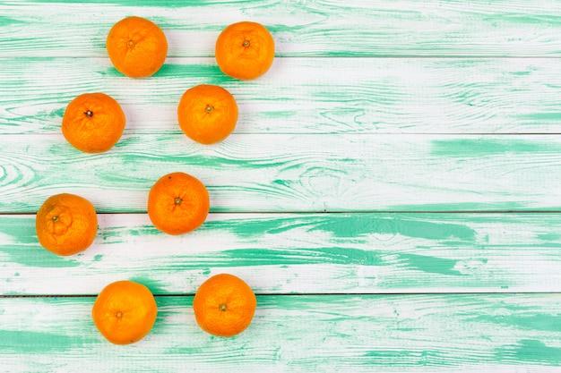 Mandarinen auf einem grünen hölzernen hintergrund