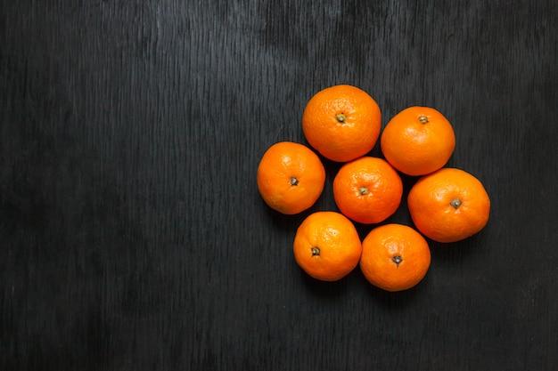 Mandarinen auf einem schwarzen hintergrund. viele frische früchte - mandarinen.