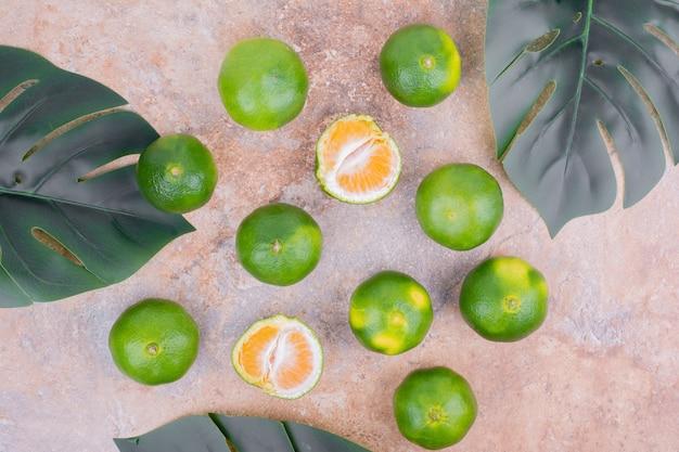 Mandarinen auf einer oberfläche mit grünen blättern