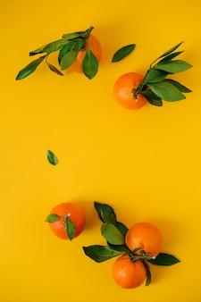 Mandarinen auf gelbem oberflächenoberseiten wiew. flach liegen.