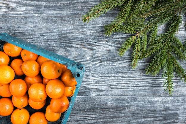 Mandarinen auf holz mit weihnachtstannenzweigen, zimtstangen, anissternen und zapfen.