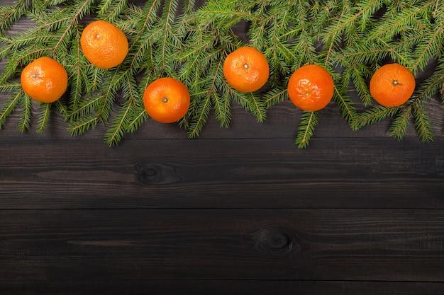 Mandarinen auf tannenbaumasten auf dunklem hölzernem