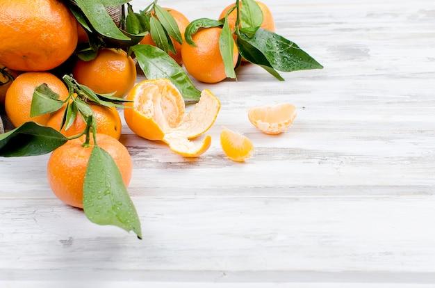 Mandarinen clementine mit blättern auf einem holztisch.