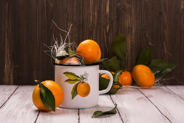 Mandarinen im retro becher des weißen emails