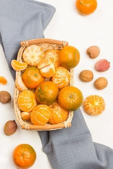 Mandarinen im weidenkorb auf grauer serviette. litschi-beeren und walnüsse auf dem tisch. weißer hintergrund. flach liegen
