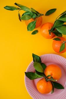 Mandarinen in der schüssel auf gelbem oberflächenoberseite wiew. flach liegen.