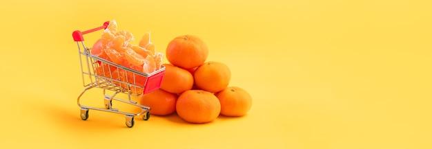Mandarinen in einem einkaufswagen über gelb