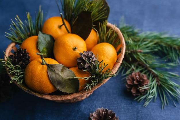 Mandarinen in einem hölzernen korb verziert mit kiefernniederlassungen