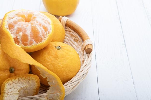 Mandarinen in einem korb auf weißen holzbrettern