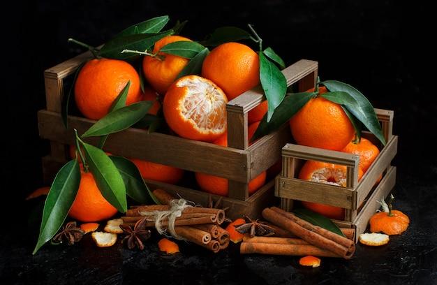 Mandarinen in einem korb und gewürze auf einem dunklen hintergrund