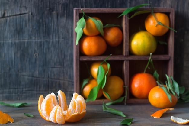 Mandarinen in einer holzkiste. rustikaler stil.