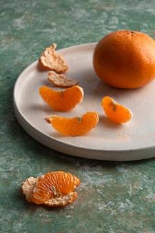 Mandarinen in keramikplatte grüner hintergrund