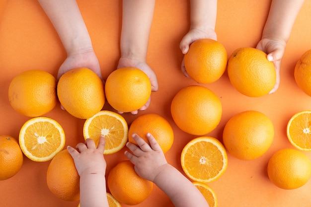 Mandarinen in kinderhänden schließen über orangen