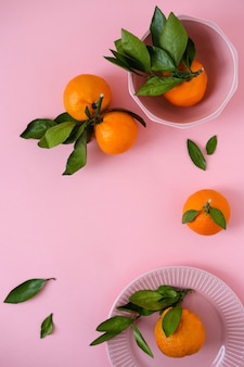 Mandarinen in rosa schüssel auf rosa oberfläche