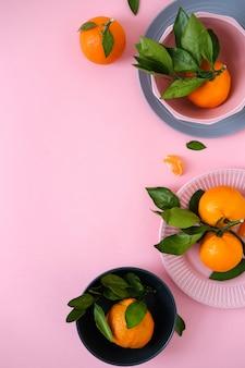 Mandarinen in schalen auf rosa oberfläche