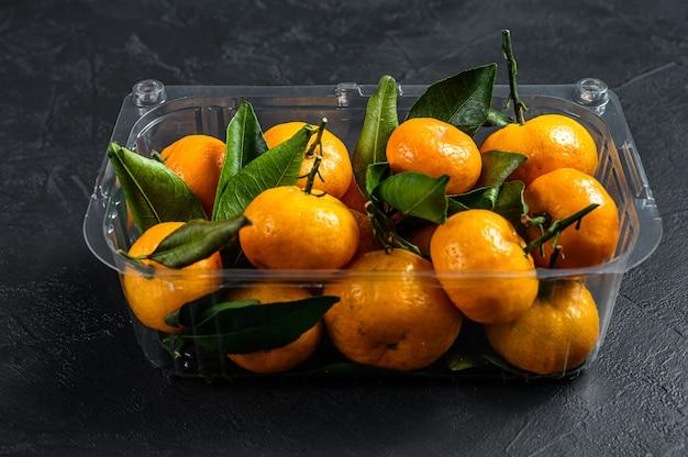 Mandarinen, mandarinen in einem plastikbehälter
