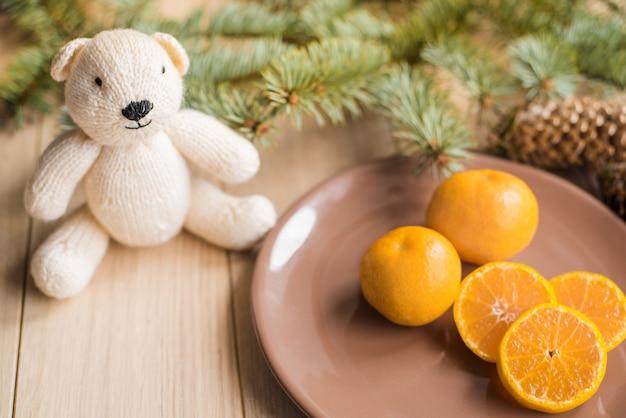 Mandarinen, mandarinen mit weihnachtsbaumasten auf hölzernem hintergrund