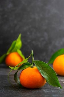 Mandarinen, mandarinenfrucht lokalisiert auf dunklem hintergrund