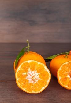 Mandarinen mit blättern auf brauner oberfläche
