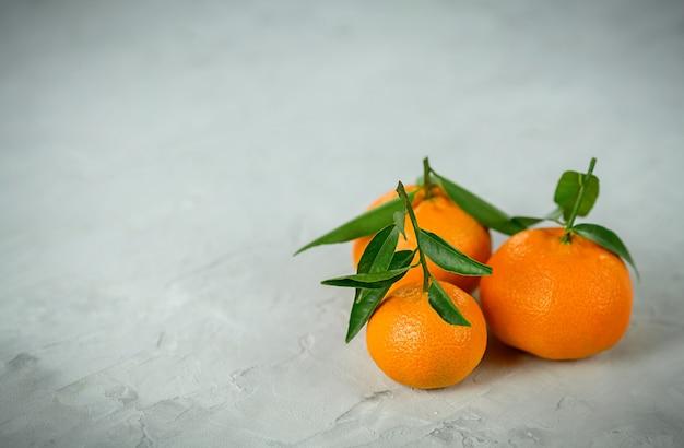 Mandarinen mit blättern auf dem grauen betonhintergrund.