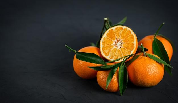 Mandarinen mit blättern auf dem schwarzen hintergrund.