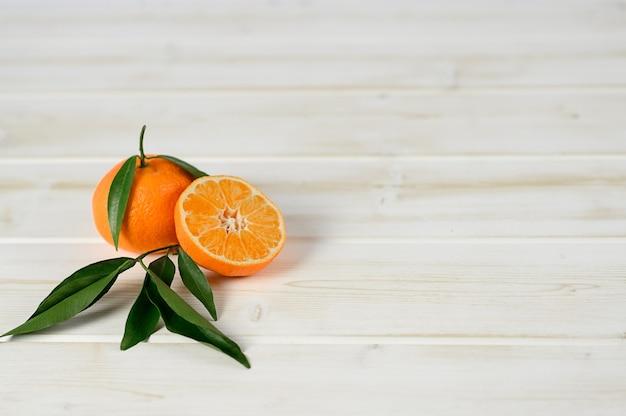 Mandarinen mit blättern auf dem weißen hölzernen hintergrund.