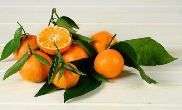 Mandarinen mit blättern auf dem weißen holztisch.