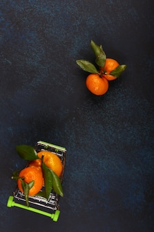 Mandarinen mit blättern auf dunkelblauem hintergrund. draufsicht, flacher stil, platz für text
