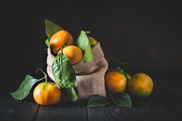 Mandarinen mit blättern auf einem altmodischen landtisch. selektiver fokus. horizontal.